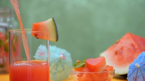 Healthy watermelon drink pouring in a clear glass decorated with a fruit piece - Summer fruit India