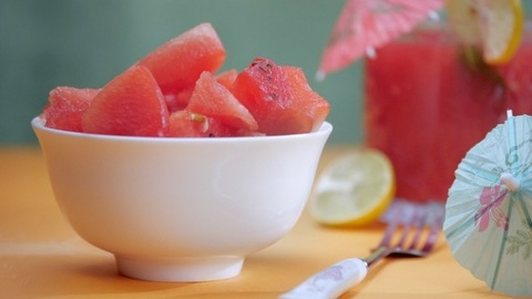 Slices of juicy watermelon falling in a porcelain bowl - tropical summer fruit