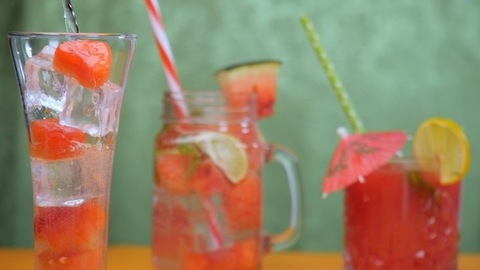 Pouring of soda water with ice cubes and watermelon pieces in a clear glass