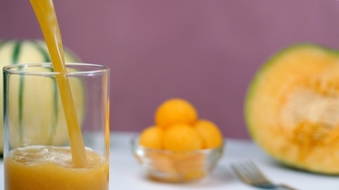 Fresh yellow muskmelon juice / drink pouring in a clear glass - nutritious diet