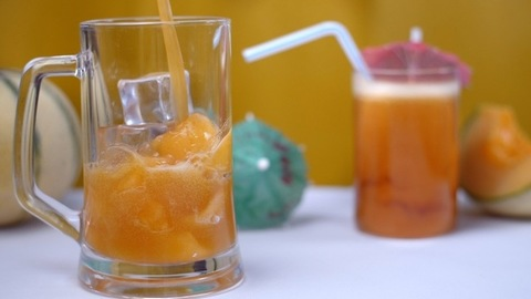 Pouring of muskmelon juice / drink in a mug with fruit slices and ice cubes - Summer drink India