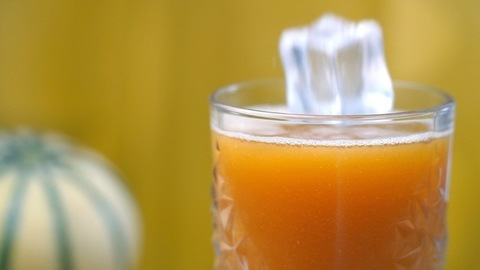 Two big ice-cubes falling / splashing inside a clear glass of muskmelon juice - Summer drink India