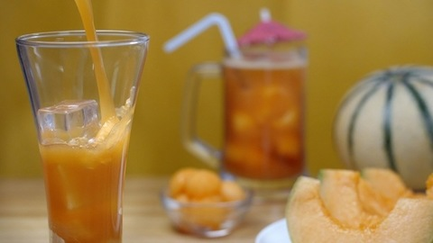 Pouring of healthy drink with fruit slices and ice cubes - nutritious food.  Summer drink India