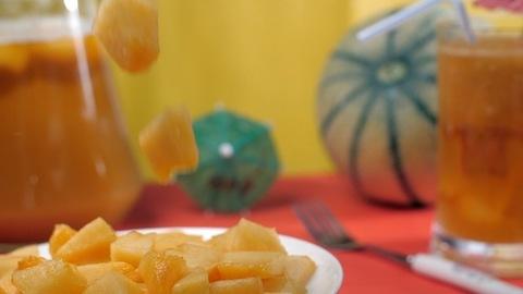 Freshly sliced muskmelon falling on a ceramic plate - healthy summer fruit