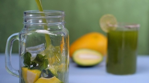 Raw mango lemonade with ice cubes and mint leaves pouring in a glass jar - Summer drink in India