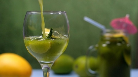 Pouring of Kairi Panna in clear glass with mint leaves and lemon slice - Aam Panna, Summer drink in India