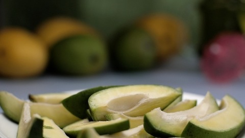 Raw mangoes on a ceramic plate rotating on a turntable - mango pickle ingredients