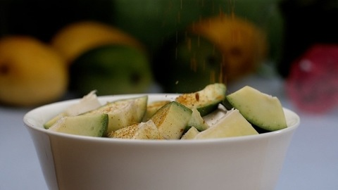 A sprinkling of spicy Masala on raw mangoes kept in a ceramic bowl - Aam Ka Achar