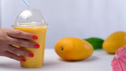 Lady's hand keeping refreshing mango shake / smoothie with a straw - Summer fruit India