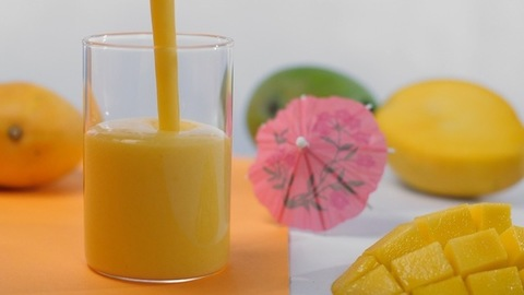 Top view of refreshing mango milkshake / Lassi poured in a clear glass - Summer drink India