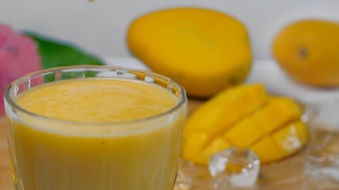 Droplets falling in a transparent glass of refreshing mango milkshake / juice - Summer drink India
