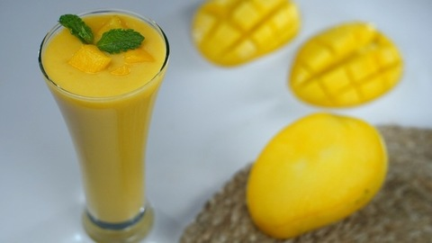 Mango smoothie topped / garnished with a fresh mint leaf - summer drink