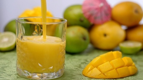 Thick mango juice / smoothie being poured into a glass - morning breakfast, Summer drink India