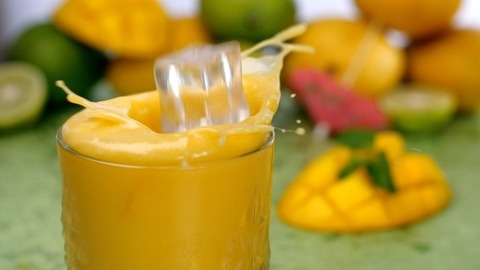 Big ice cubes falling / splashing into a glass full of refreshing mango smoothie - Summer drink India
