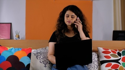 Portrait of a Indian female entrepreneur in a black T-shirt doing her office work on a laptop