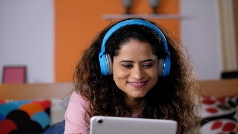 Portrait of a pretty Indian lady watching a movie on a tablet - Online movie, OTT