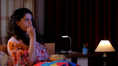 Portrait of a young Indian woman with long black hair eating chips while watching web series on television