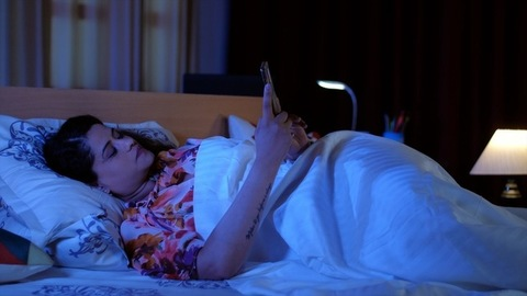 Young woman using mobile and chatting at night - leisure time. Long-distance relationship