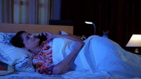 Portrait of a beautiful Indian girl receiving a call on her mobile while lying down in bed, late-night call with boyfriend