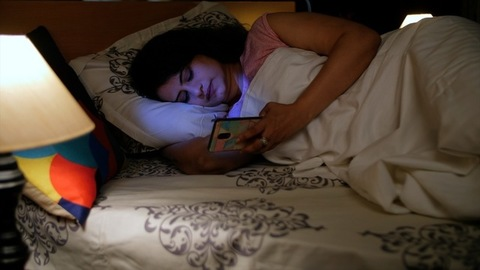 Portrait of a pretty woman using her smartphone lying down on the bed at night