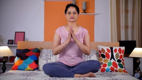 A pretty lady in casual clothes doing meditation - Yoga, Namaste pose, healthy lifestyle