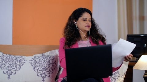 A cheerful businesswoman with white earphones talking to her colleague on a laptop