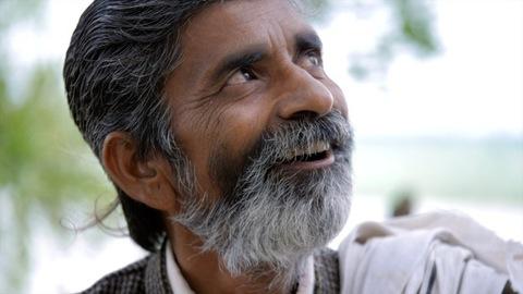 Indian Hindu male with grey-black hair and beard