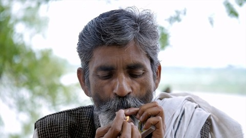 An old man smoking a beedi - local form of a cigar leaf filled with tobacco
