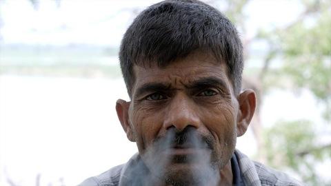 An Indian poor villager enjoying smoking a beedi in his free time