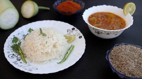 Fresh coriander leaf / Dhania falling on a plate of white rice with green chilies