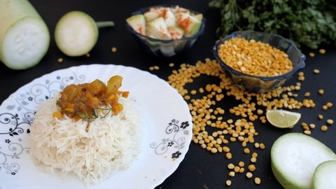 Homemade delicious Lauki Sabzi / curry falling on a plate of rice and fresh Dhania