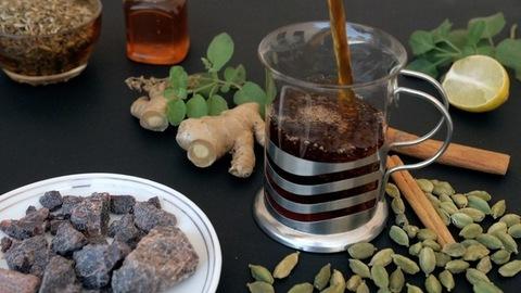 Tea seasoned with Tulsi leaves pouring in a clear mug - health and medicine - Black tea