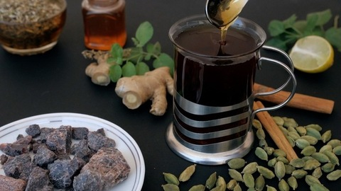 A spoonful of organic honey and Tulsi leaves in a clear glass of herbal black tea