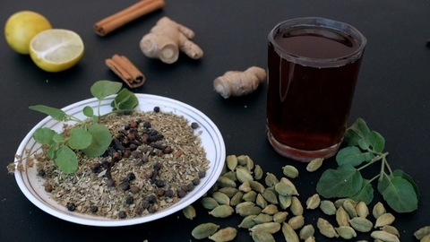 Whole black pepper and cloves falling on a plate of dried tea leaves with Tulsi Patta