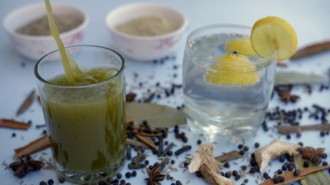 Refreshing Jaljeera drink with fresh mint leaves and Boondi pouring in a clear glass
