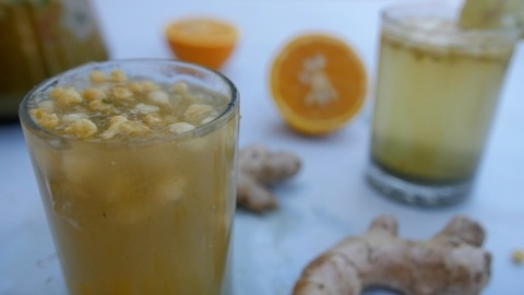A freshly cut lemon half being dropped in a glass of cool summer drink - Jaljeera