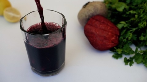 Beetroot juice garnished with mint leaves and slices pouring in a clear glass