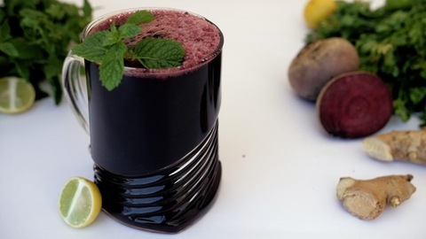 A sweet vegetable juice rich in vitamin seasoned with mint leaves in a clear mug