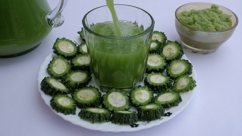 A glass of bitter gourd juice and sliced Karela beautifully decorated on a plate