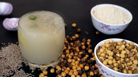 Chunks of ice falling in a glass of Sattu drink decorated with chilies and lemon