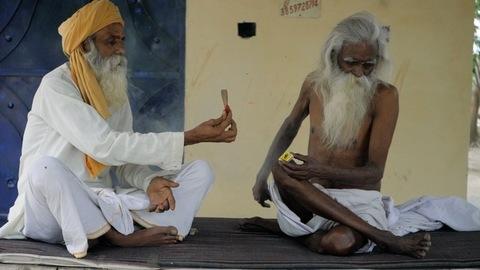 Elderly men in white Kurta Pajama smoking together at home - lifestyle and addiction