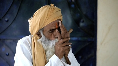 An Indian old man with an orange Tika on his forehead smoking