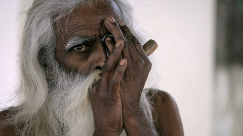 An elderly Indian man from a rural village relaxing alone while smoking a pipe