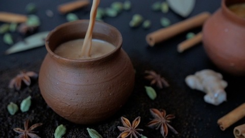 Tasty homemade boiling hot tea poured in traditional clay cups - Indian culture