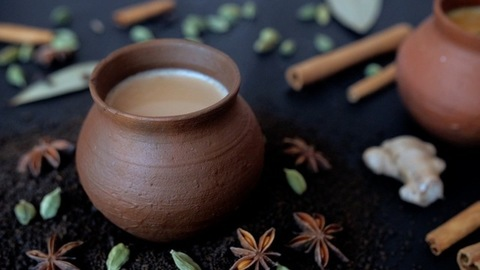 Smoke coming out of steaming hot and flavored milk tea served in an earthen pot