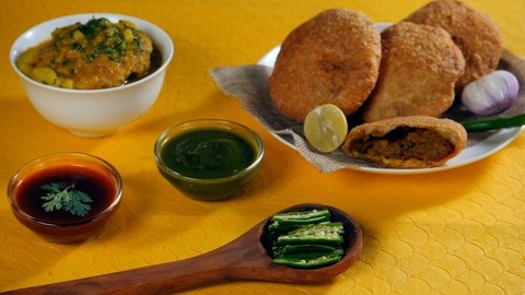 Hands keeping spicy green chilies with a plate of tasty Kachoris and raw onions - Street Food India