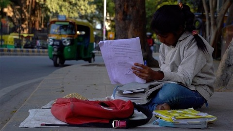 Connaught Place, New Delhi - India: Poor urban girl preparing for her examinations sitting on a pavement under a tree