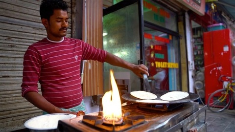 New Delhi, India - June 15, 2020: Portrait of an Indian vendor making fresh flatbreads / Rotis in a Dhaba