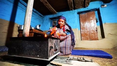 Himachal Pradesh, India - July 20, 2020: Portrait of an elderly mature woman lighting her Chulha