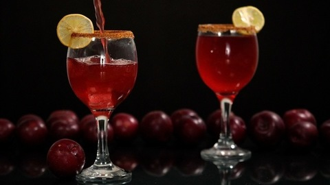 Fresh plum drink decorated with a slice of lemon and an ice cube pouring in a glass - Indian summer fruit